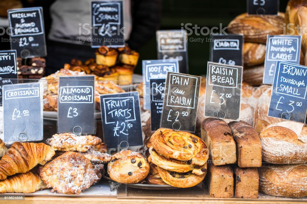 Close up of huge selection of pastries and bread on bakery stall at food market - Foto stock royalty-free di Affari