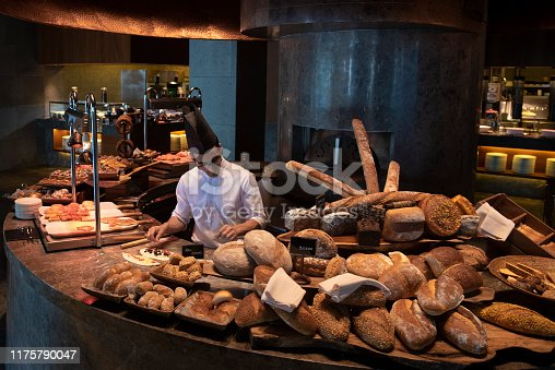 Close up of huge selection of pastries and bread on bakery stall.