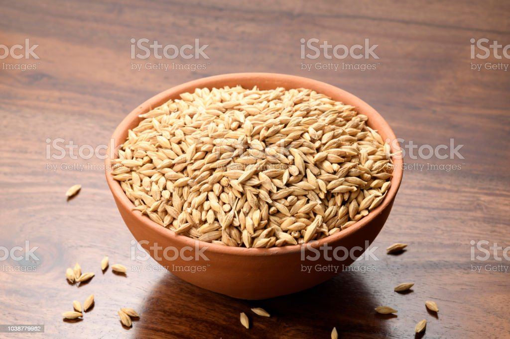Close up of Hulled Barley in a Earthen Bowl on Wooden Background stock photo
