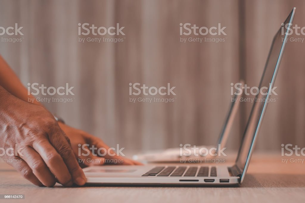 Close up of human hand using laptop for work in office - Royalty-free Adult Stock Photo