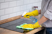 Close up of human hand with protective gloves cleaning induction hob with rag and holding spray bottle. Homework