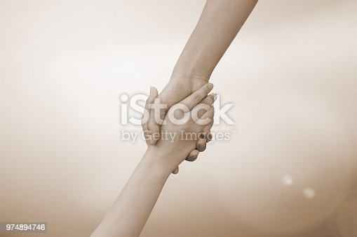 istock close up of human hands holding together for helping concept in sepia color. 974894746