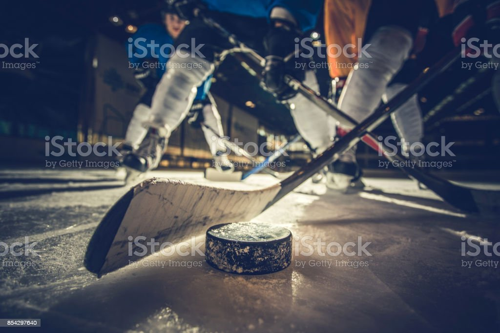 Close up of ice hockey puck and stick during a match. stock photo