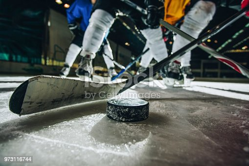 Close up of hockey puck and stick during a match with players in the background.