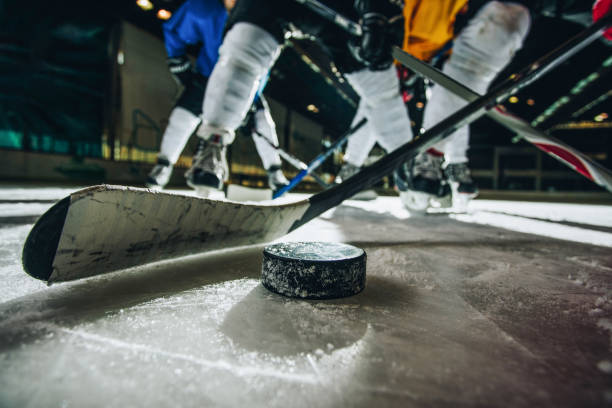 close up of ice hockey puck and stick during a match. - hockey puck stock photos and pictures