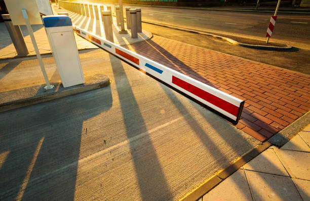 Close up of illuminated by warm sunset light barrier gate entrance Perspective view with long shadows boundary stock pictures, royalty-free photos & images