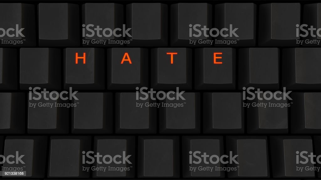 Close Up of Illuminated Glowing Keys on a Black Keyboard Spelling Hate stock photo