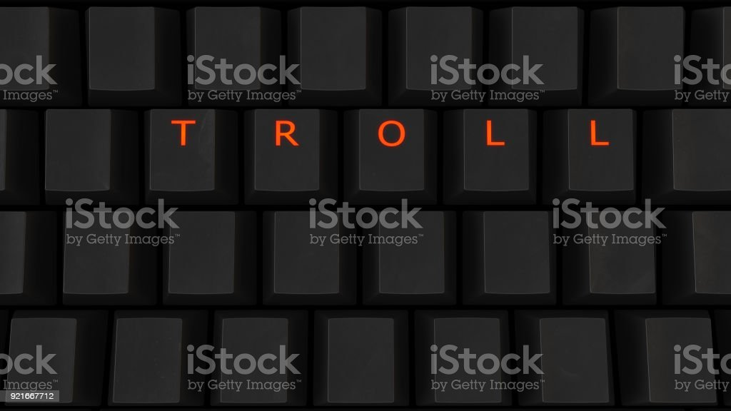 Close Up of Illuminated Glowing Keys on a Black Keyboard Spelling Troll stock photo