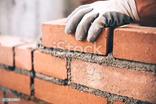 istock Close up of industrial bricklayer installing bricks on construction site 622800884