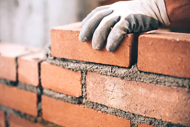 primo piano del muratore industriale che installa mattoni in cantiere - costruire foto e immagini stock