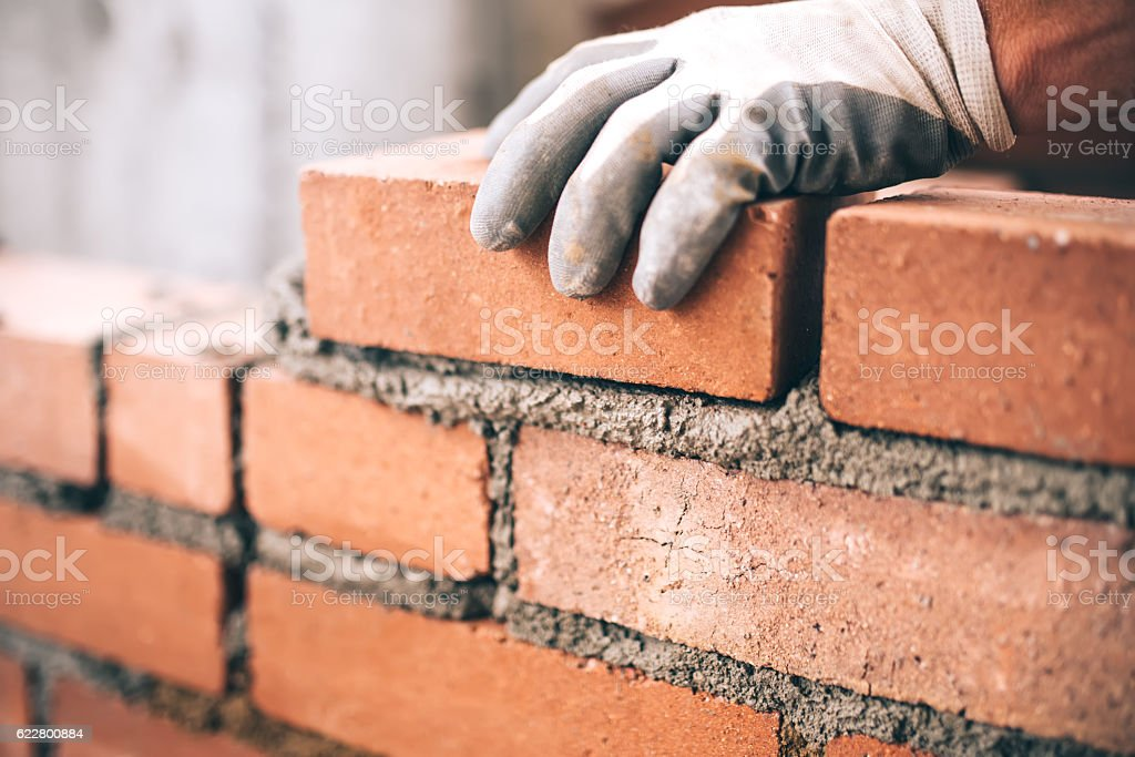 Close up of industrial bricklayer installing bricks on construction site 스톡 사진