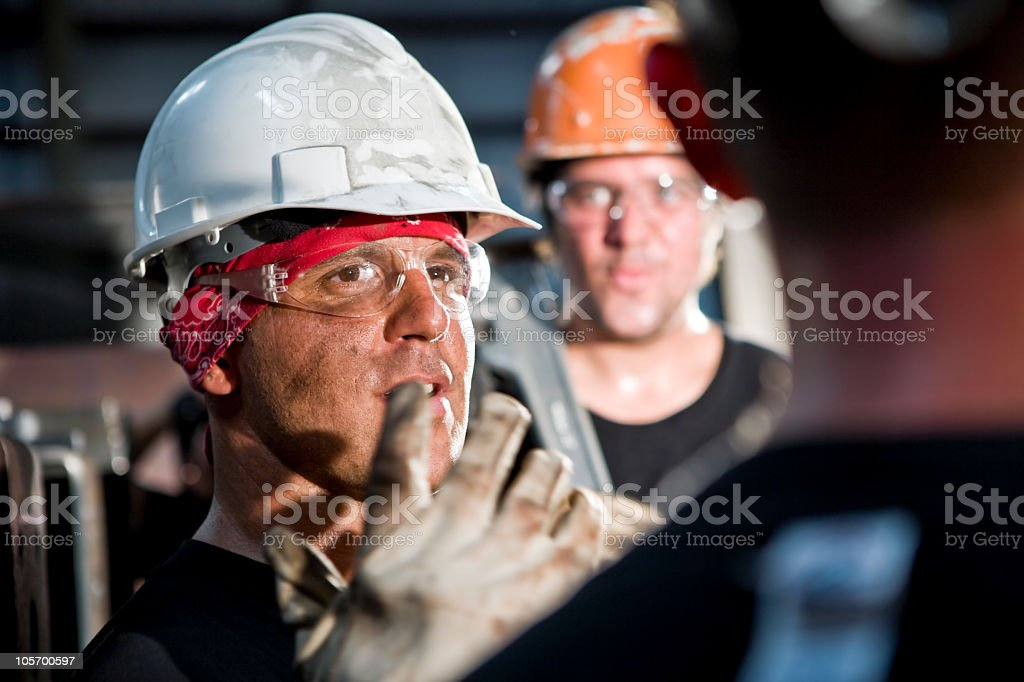 Close up of industrial foreman conversing in factory royalty-free stock photo