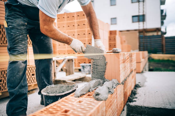 Close up of industrial worker, bricklayer installing bricks on construction site stock photo