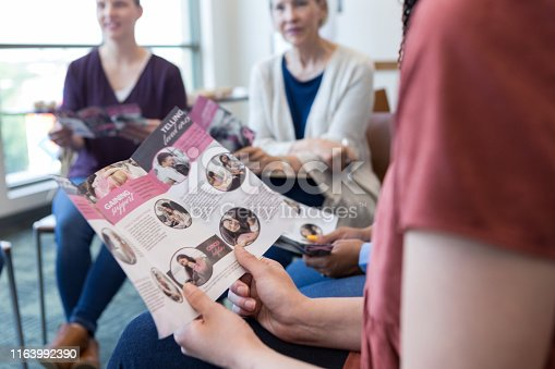 1055095320 istock photo Close up of informational brochure held by woman at meeting 1163992390