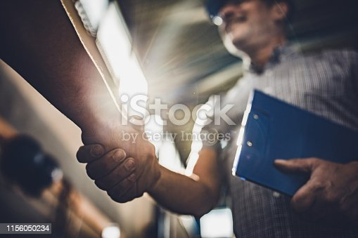 Low angle view of manager greeting unrecognizable person in industrial building.