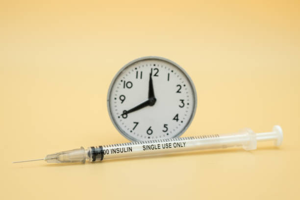 close up of insulin syringe for blood sugar level control with vintage round clock using as medicine, diabetes, glycemia, health care and people concept. - flu shot zdjęcia i obrazy z banku zdjęć