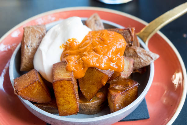 """close up of inviting bowl of traditional spanish """"patatas bravas"""", appetizer made with potatoes and paprika and garlic sauce stock photo"""