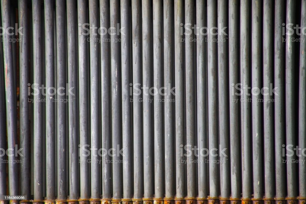 Close up of isolated grey weathered iron pipes in a row