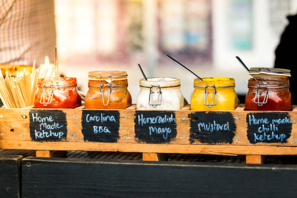 Close up of jars of different sauce in a row at outdoor burger stall stock photo