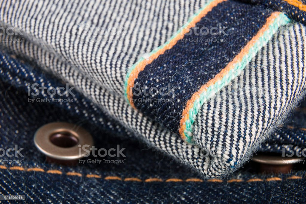 Close up of jeans fragment with button. Denim texture. Selvage. Lizenzfreies stock-foto