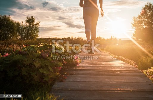 Close up of unknown woman running in park at sunset.
