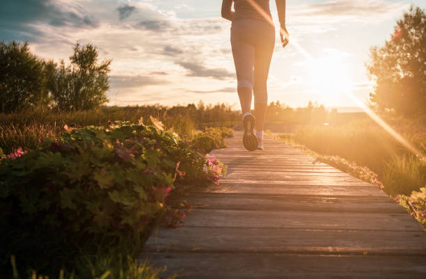 Close up of jogging. Close up of unknown woman running in park at sunset. wellbeing stock pictures, royalty-free photos & images