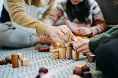 Close up of joyful Asian parents sitting on the floor in the living room having fun and playing wooden building blocks with daughter together