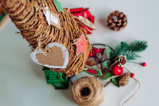 Close up of kids handmade corrugated cardboard decorations on wooden Christmas tree