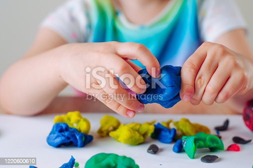 Close up of kids hands molding colorful child's play clay. Learning educational activities for children at home or in kindergarten.