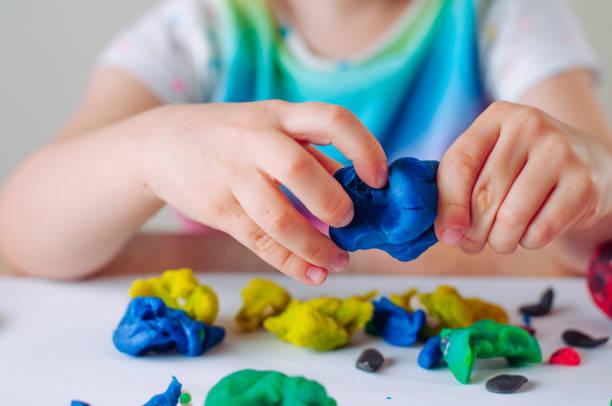 z bliska ręce dzieci formowania kolorowe dziecko grać gliny - glina zdjęcia i obrazy z banku zdjęć