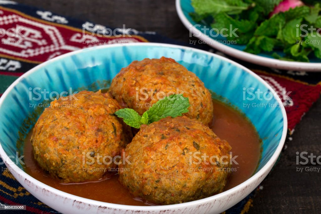 Close up of Koofteh Tabrizi Large Meatballs Stuffed With Dried Fruits, Berries And Nuts In Tomato Turmeric Broth A Traditional Azeri And Iranian Dish Served In Turquoise Bowl stock photo
