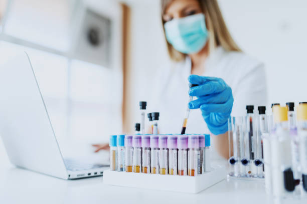 Close up of lab assistant in uniform, with mask and rubber gloves holding test tube with blood sample while sitting on chair and typing on laptop. Selective focus on test tubes. Close up of lab assistant in uniform, with mask and rubber gloves holding test tube with blood sample while sitting on chair and typing on laptop. Selective focus on test tubes. cure stock pictures, royalty-free photos & images