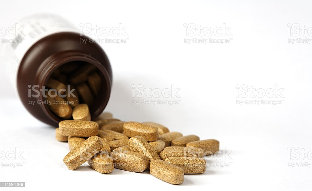 Close up of laid out brown vitamins on white background royalty-free stock photo