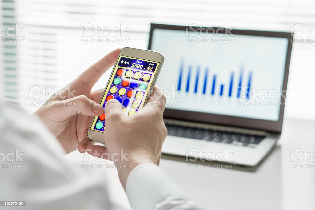 Close up of Lazy and unproductive office worker playing mobile game with smart phone during business hours. Avoiding his work. Useless and bored man doing nothing and forget his job. stock photo