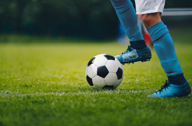 Close up of legs and feet of football player in blue socks and shoes running and dribbling with the ball. Soccer player running after the ball. Sports venue in the background Close up of legs and feet of football player in blue socks and shoes running and dribbling with the ball. Soccer player running after the ball. Sports venue in the background leisure equipment stock pictures, royalty-free photos & images