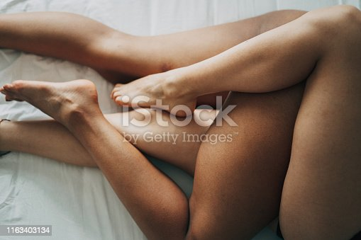 Sexy legs on lesbian couple in the bed