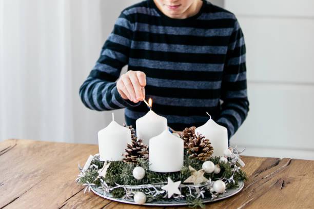 nahaufnahme der beleuchtung der ersten kerze am adventskranz am ersten sonntag im dezember. feiern weihnachten, schweizer tradition. - weihnachten 7 jährige stock-fotos und bilder