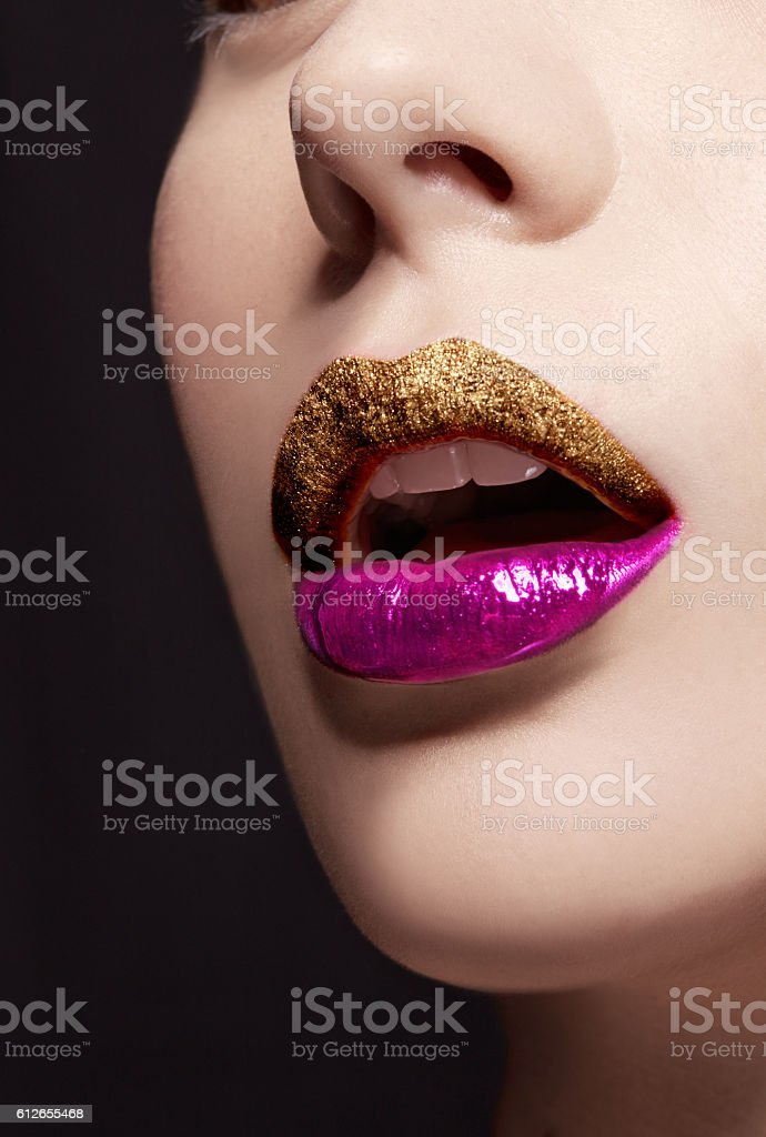 Close up of lips. Gold violet lipstick. Cosmetic makeup image. stock photo
