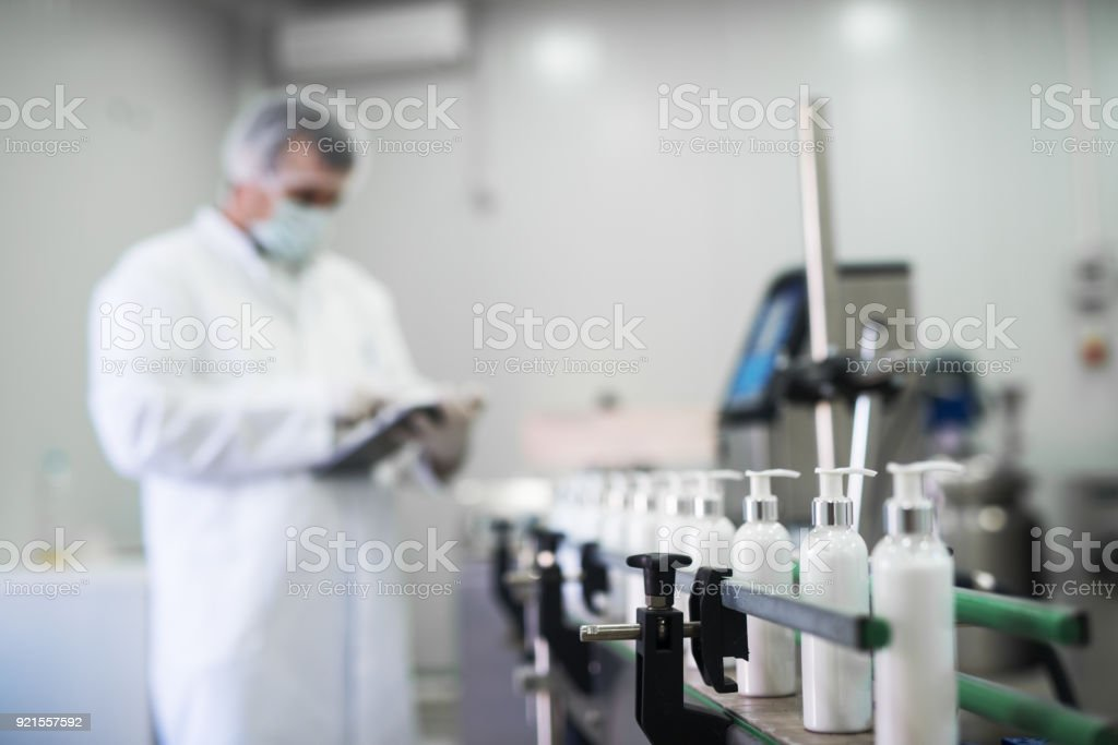 Close up of liquid soap going on a production line in front of cosmetics fabric worker typing on a tablet. stock photo