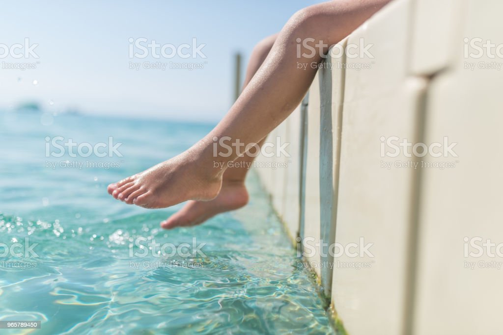 Close up of little caucasian child legs near sea water - Royalty-free Beauty Stock Photo