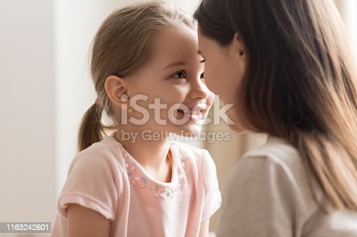 Close up of cute little daughter cuddle with young mom look in eyes enjoy sweet time together, smiling preschooler girl have tender moment with mother or nanny showing love and affection