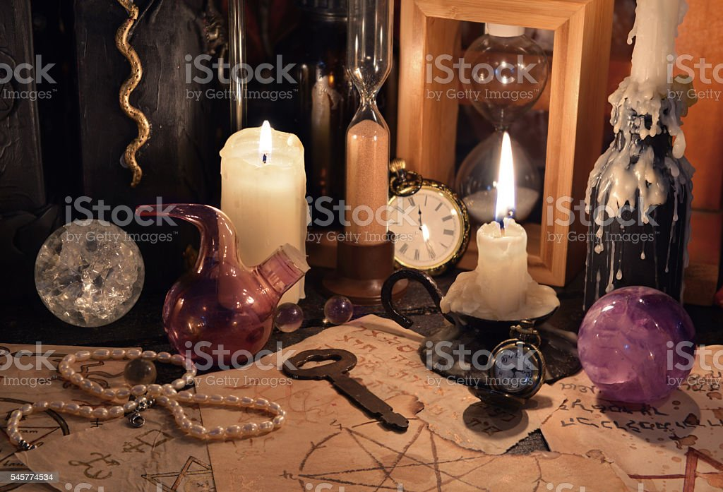 Close up of magic objects and candles on witch table stock photo