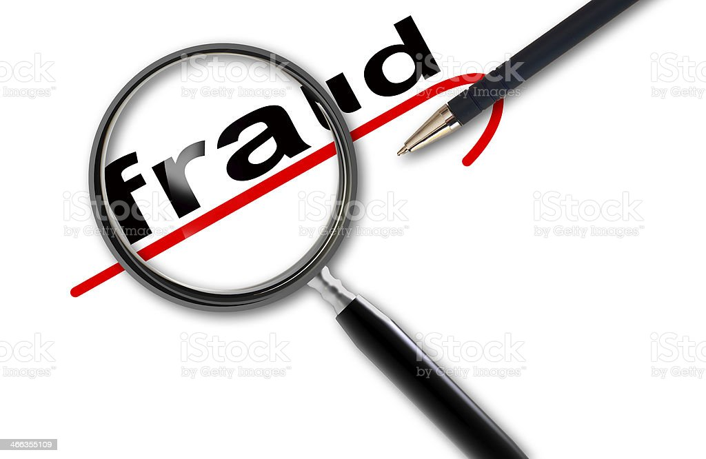 Close up of magnifying glass on fraud stock photo