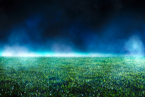 Close up of maintained lawn at football stadium. Night low view with abstract light effects. Iluminated mist.