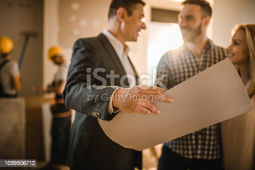 istock Close up of male architect analyzing housing plan with a couple. 1039506712