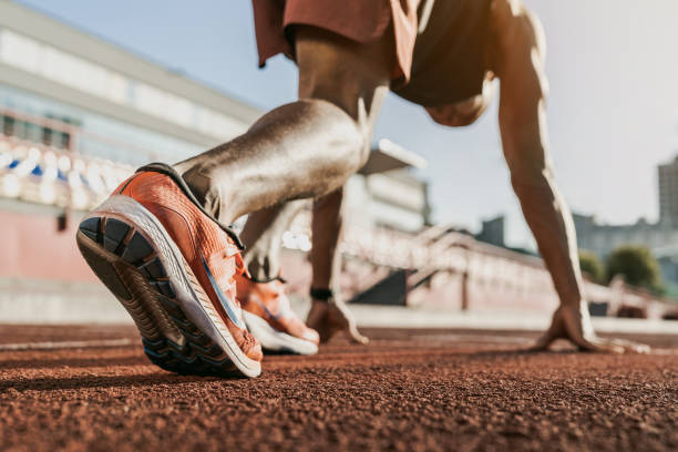 Close up of male athlete getting ready to start running on track . Focus on sneakers Running, Sport, Sprinting, Athlete, Exercising race distance stock pictures, royalty-free photos & images