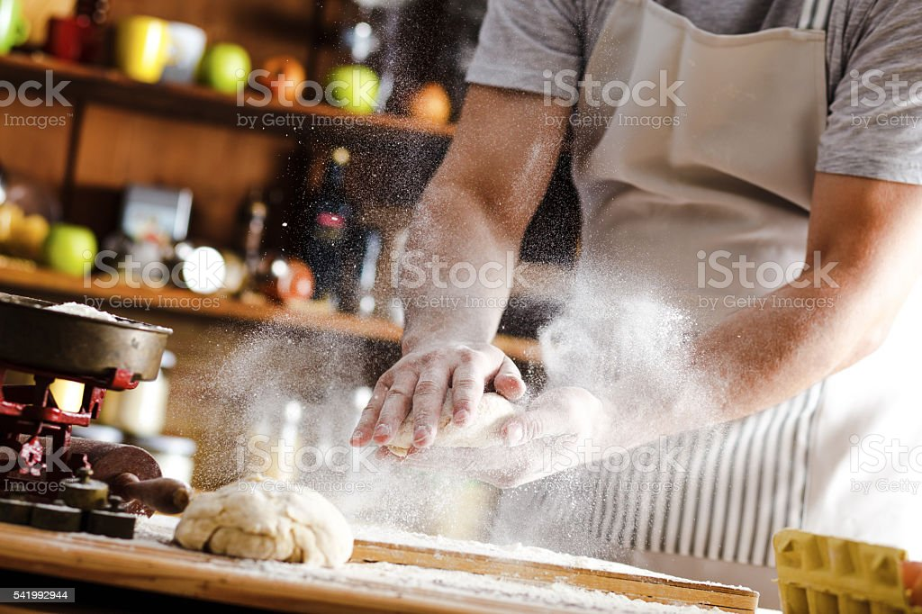 Close up of male baker hands kneading dough - Photo
