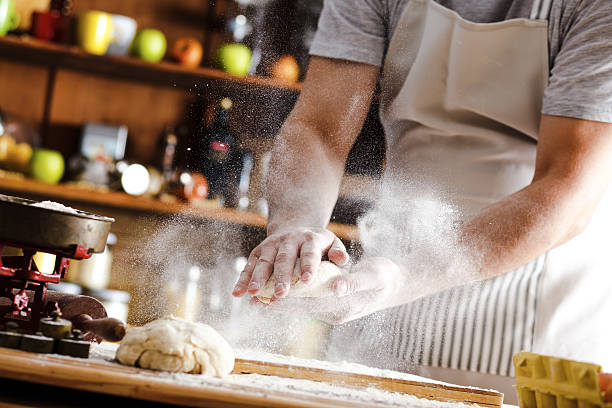 close up of male baker hands kneading dough - bakery stockfoto's en -beelden