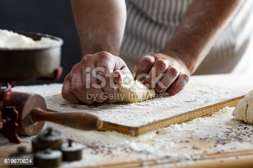 istock Close up of male baker hands kneading dough 619670624