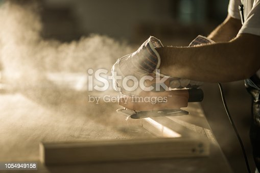 istock Close up of male construction worker working with sander on a wood plank. 1054949158